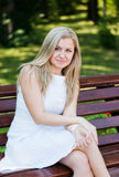 Young woman sitting on the bench. In park Stock Photos