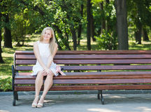 Young woman sitting on the bench. In park Royalty Free Stock Photos