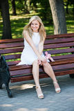 Young woman sitting on the bench. In park Stock Images