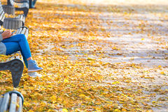 Young woman sitting on a bench in park. Young woman sitting on a bench in autumn park with yellow fallen leaves royalty free stock photos