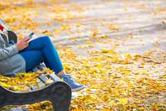 Young woman sitting on a bench in park. Young woman sitting on a bench in autumn park with yellow fallen leaves royalty free stock images
