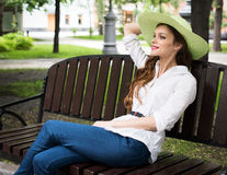Young woman sitting on the bench in park Royalty Free Stock Images