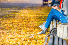 Young woman sitting on a bench in park. Young woman sitting on a bench in autumn park with yellow fallen leaves stock photos