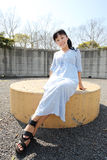 Young woman sitting on a bench. Portrait of young japanese woman sitting on a bench Royalty Free Stock Images