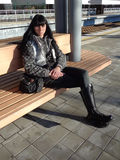 Young woman sitting on bench at railway platform. Young modern woman with black hair sitting on bench waiting for the train Stock Image