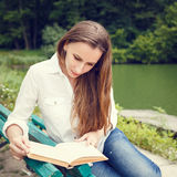 Young woman sitting on the bench and reading book Stock Image