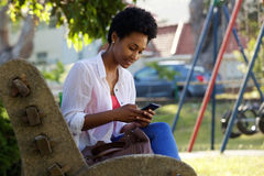 Young woman sitting on a bench sending text message Stock Photos
