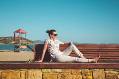 Young woman sitting on a bench and sun tanning. Young woman sitting on a bench by the beach and sun tanning Royalty Free Stock Images