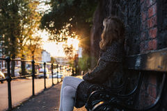Young woman sitting on bench at sunset Stock Photos