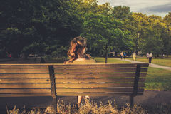 Young woman sitting on a bench at sunset Stock Photos