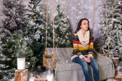 Young woman sitting on a bench or a swing in a snow-covered park Stock Images