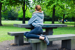 Young woman sitting on bench by table in park Stock Photos