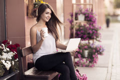 Young Woman Sitting On The Bench And Using Laptop Royalty Free Stock Photo