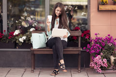 Young Woman Sitting On The Bench And Using Laptop Royalty Free Stock Photos