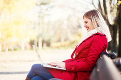 Young woman sitting on the bench, using a laptop. Smiling Stock Image