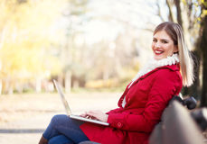 Young woman sitting on the bench, using a laptop. Smiling Stock Photos