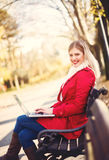 Young woman sitting on the bench, using a laptop Stock Photos