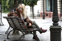 Young woman sitting on a bench Royalty Free Stock Photos
