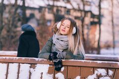 Young Woman Sitting on Bench in Winter Royalty Free Stock Photography