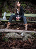 Young woman sitting at the bench in woods Stock Image