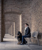 Young woman sitting on a bench with your best four-legged friend. Quietly peering into the camera. Architectural arch repeating in the background, with brick Stock Image