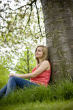 A young woman sitting beneath a tree, looking thoughtful royalty free stock images