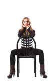 Young woman sitting on a black chair. Thin beautiful woman sitting on a black chair with her hands placed on her cheeks - isolated on white Stock Photography