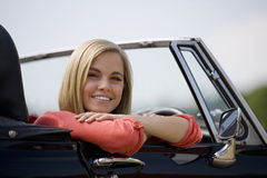 A young woman sitting in a black sports car Stock Photography