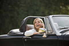 A young woman sitting in a black sports car speaking on a mobile phone Stock Photos