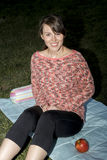 Young woman sitting on a blanket outdoors at night Royalty Free Stock Photos