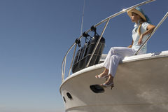 Young woman sitting on boat. Young woman sitting on edge of boat against a blue sky Royalty Free Stock Image