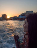 Young woman sitting on the boat and enjoying a view of the sun coming down Royalty Free Stock Photo