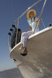 Young woman sitting on boat. Young woman in hat sitting on edge of boat, legs hanging over edge Stock Image