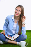 Young woman sitting with book on grass Stock Images