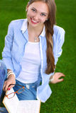 Young woman sitting with book on grass Stock Photo