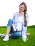 Young woman sitting with book on grass Royalty Free Stock Images