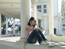 Young woman sitting beside books in colonnade, using mobile phone, smiling Stock Photography
