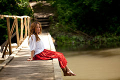 Young woman sitting on the bridge Royalty Free Stock Image