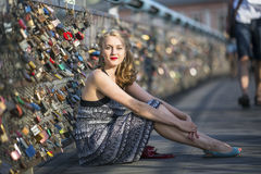 Young  woman sitting on the bridge of love with padlocks. Stock Photos