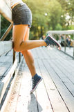 Young woman sitting on a bridge railing in jeans sneakers Stock Photography