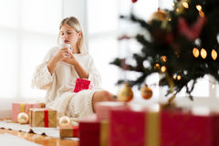 Young woman sitting in a bright room, drinking coffee. Christmas tree Stock Image
