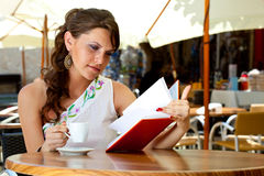 Young woman is sitting in the cafe. Young brunette woman is drinking coffee and reading book in a cafe Stock Images