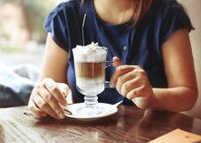 Young woman sitting in a cafe with a cup of coffee latte Royalty Free Stock Photo