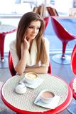 Young woman sitting in the cafe with a cup of tea Royalty Free Stock Photos