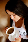 Young woman sitting in a cafe drinking coffee Stock Images