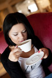 Young woman sitting in a cafe drinking coffee Royalty Free Stock Images