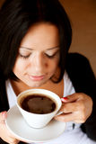 Young woman sitting in a cafe drinking coffee Royalty Free Stock Photos