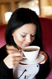 Young woman sitting in a cafe drinking coffee Stock Photos