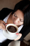 Young woman sitting in a cafe drinking coffee Stock Image