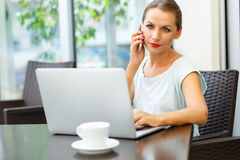 Young woman sitting in a cafe with a laptop and talking on the c Royalty Free Stock Images